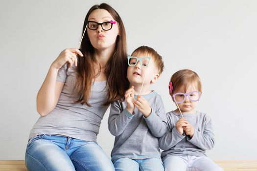 Portrait of a happy mother and her two little children - boy and girl. Happy family with funny photo props cardboard glasses against a white background