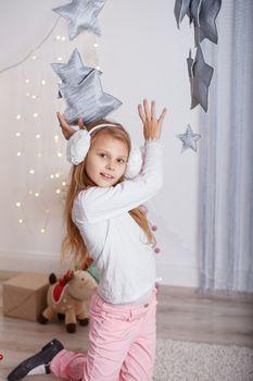 Portrait of a beautiful little girl in a in earmuffs in the inte