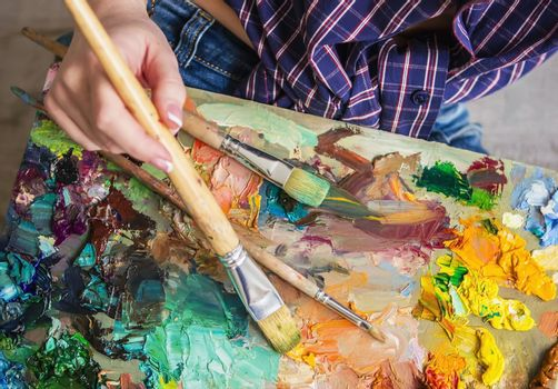 Brush and oil paints on a palette, paint a picture of the artist's hands, texture mix paint in different colors. Artist holding a palette with paint, brushes and palette knife