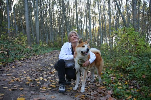 Lady with her dog posing in the forest