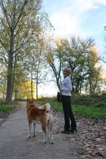 Lady with her dog posing on the forest path