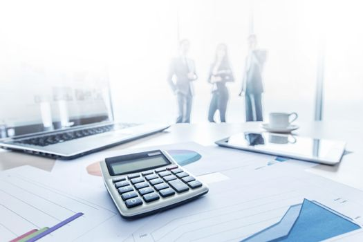 Financial data documents, calculator and laptop, three businessmen standing on background