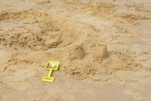 Kids spade by broken down sandcastle