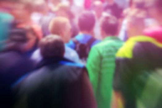 Pedestrians on the street as blur urban background