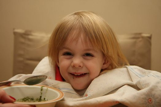 Young girl enjoys eating nettle chowder