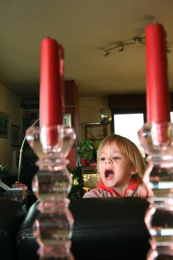 Young girl clowning between two candles