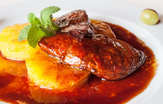 Luxuriously served roasted goose liver over orange slices with sauce and fresh mint meal.