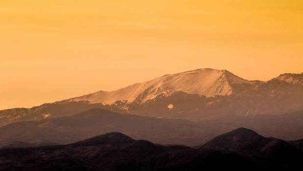 mountains at sunset with snow