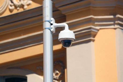 Dome Type Outdoor CCTV Camera on Street Lamp in Nice, Architecture of a Church in the Background