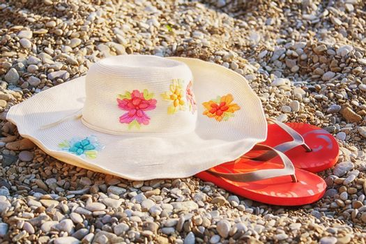 hat with wide brim and pink flip-flops on beach