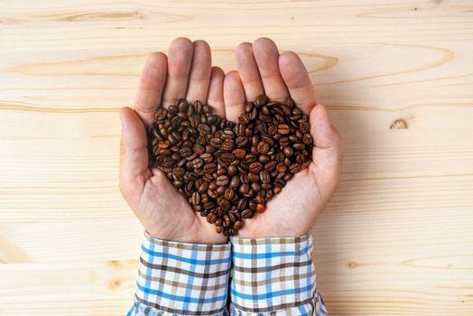 Handful of roasted coffee beans heart shaped pile