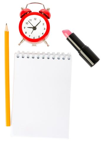 Open copybook with lipstick and alarm clock