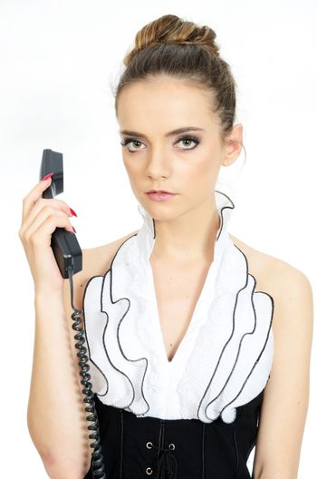 Businesswoman with telephone in her hand. Young female model with elegant office clothes. Kind and serious face expression.