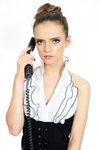 Female model holding cable phone. Young girl with serious face expression. Elegant office lady.