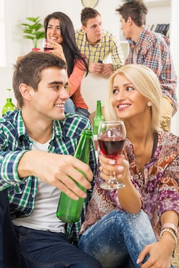 Young couple at a home party, sit on the floor and knocking with drinks, in the background you can see their friends who are sitting on the couch.