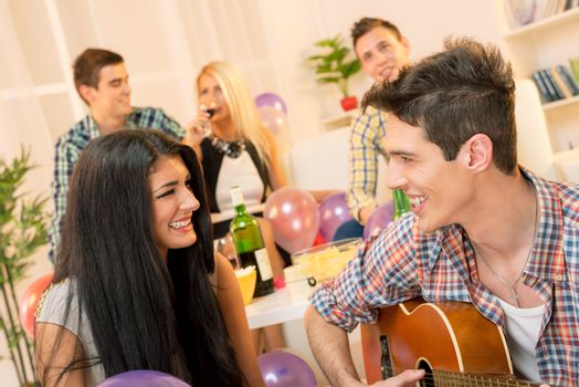 A young man with an acoustic guitar, at home party, courting a pretty girl playing to her. In the background you can see young people sitting on the couch and enjoy the atmosphere of home party.