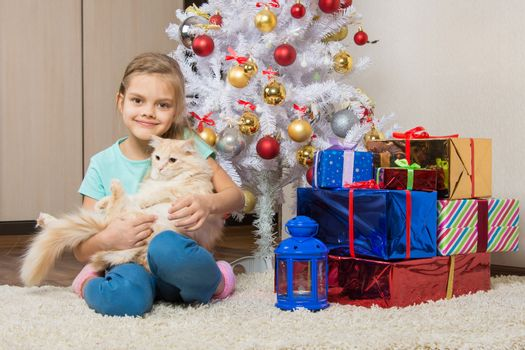 Joyful seven year old girl with a cat sitting under the Christmas tree with gifts