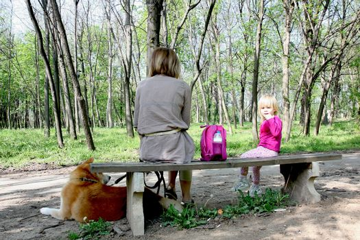 Grandmother with granddaughter and dog enjoying on the bench