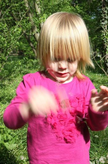 Portrait of young girl  playing with dandelion