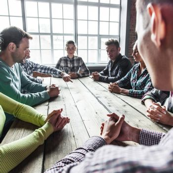 Modern business meeting concept, people on casual clothes sitting around wooden table