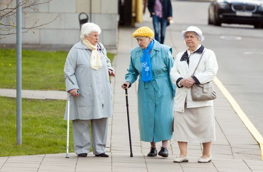 VILNIUS, LITHUANIA – MAY 2, 2016: Three aged senior women walking on the street and talking. Real life editorial picture taken in Vilnius, Lithuania