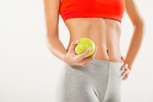 Perfect woman body. Woman holding apple. Dieting concept. White background.