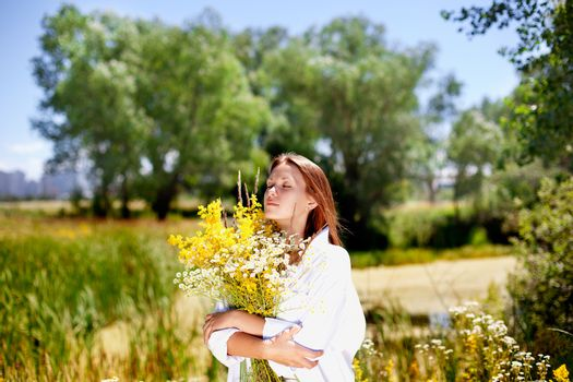 The girl holds a bouquet of wild flowers in hand.Attractive girl.a Woman
