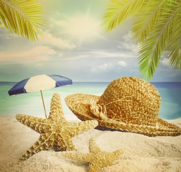 Sandy beach, straw hat and starfish in summer