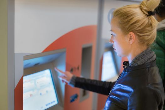 Woman buying metro ticket at vending machine.