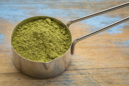 measuring scoop of organic matcha green tea powder against grunge wood