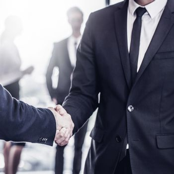 Handshake in front of business people team in office