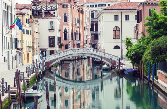 Bridge over canal in Venice, Italy. Traditional architecture also reflected in the water