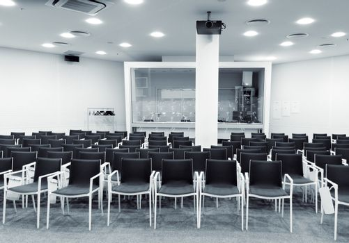 Modern press conference room with empty seats and multimedia equipment. Monochrome indoors picture