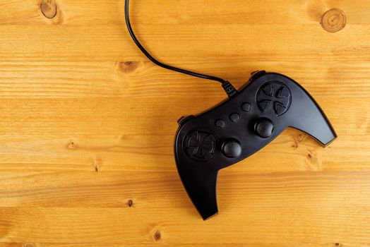 Gamepad controller on wooden desk, flat lay top view