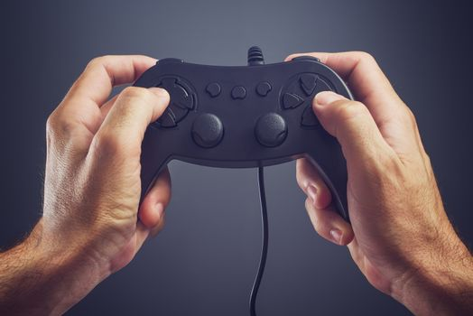 Man using game pad controller to play video games