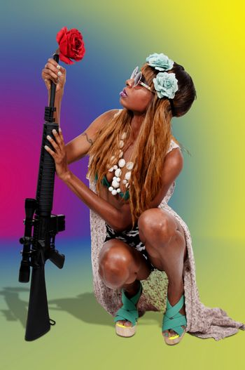Beautiful young woman hippie with a rifle and a flower