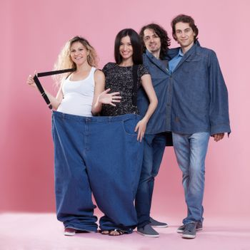 Portrait of a young pregnant women and young men wearing very large clothing. Conceptual image about weight loss themes.