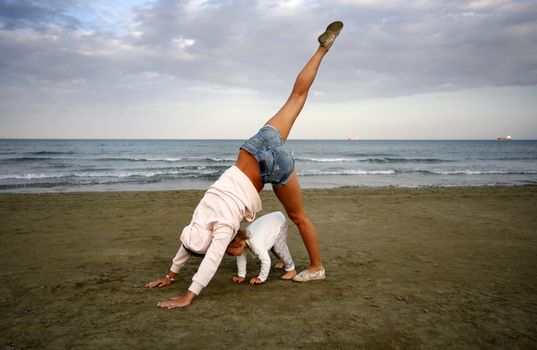 Young woman with small douther practicing yoga on the sea beach at sunset