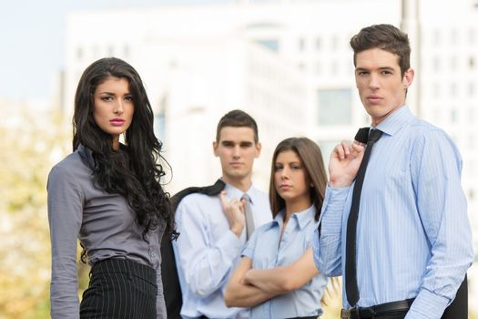 Two couples of young handsome business people, elegantly dressed, standing outside, with a serious expression on their faces looking at the camera. In the background looms large office building.