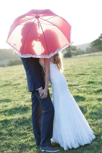 Married couple kissing under an umbrella, showing a sweet shadow of a kiss.