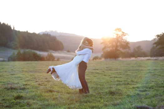 Beautiful married couple showing an embrace full of romance and love, in the middle of a field.