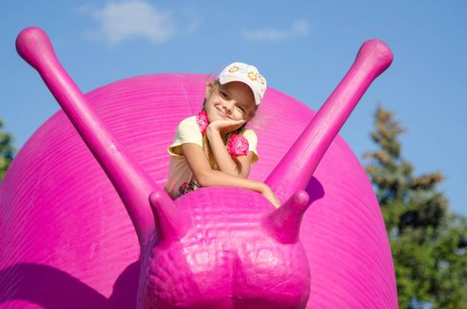 Moscow, Russia August 10, 2015: Six-year girl on a pink snail, exhibit ENEA in Moscow