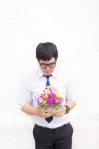Waiting for his girlfriend. Close up of handsome young man holding bouquet of flowers stand in front of the concrete wall .