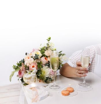 Two glasses with champagne, boutonniere with roses and cookies