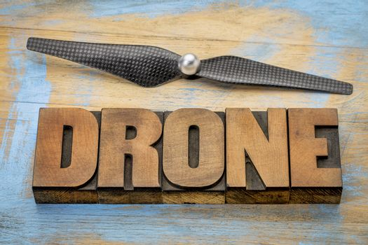 drone word abstract in vintage letterpress  wood type with a drone propeller