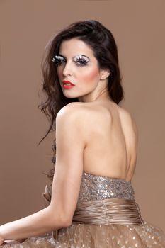 Stunning beautiful brunette in an elegant dress, looking over shoulder.