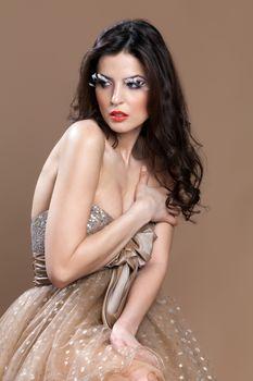 Stunning beautiful brunette in an elegant dress, embracing herself gracefully.
