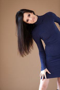 Studio portrait of a lovely brunette arching toward the camera left.
