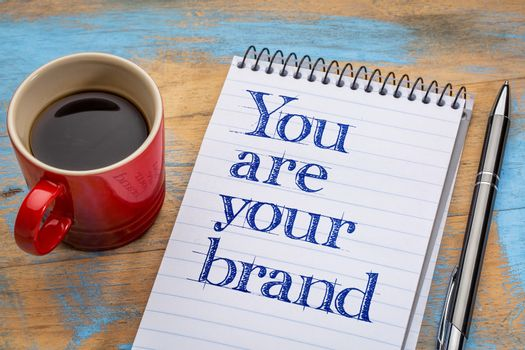 You are your brand - motivation text in spiral notebook with a cup of coffee
