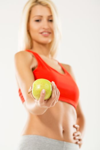 Woman holding apple. Focus on apple. Dieting concept. White background.